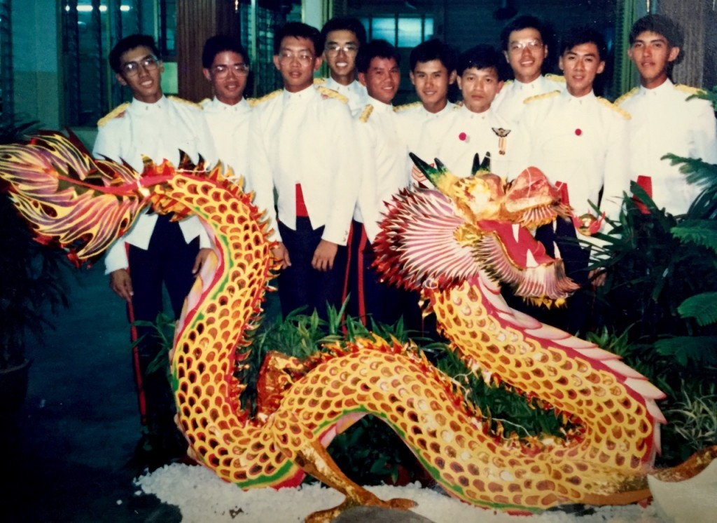 """1988 - While serving my National Service as a cadet, one of my instructor and I jointly made a dragon lantern for our graduation """"Dining-in"""". We were in """"Delta"""" Company, which was represented by """"Dragon"""". He made the dragon's skeleton using wire while I put on its skin using paper. I'm veryglad I managed to get a photo of it, because it was sheer hard work for me (I'm on the extreme left of the photo, next to thedragon's tail). As a cadet,there was already verylittle rest time in between trainings, yet I had to carve it out further to make thedragon, either during weekends or when everyone else wasasleep."""